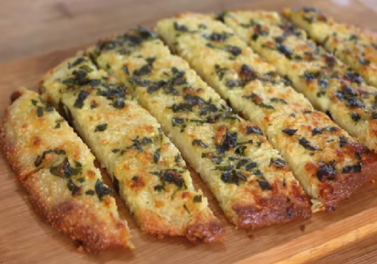 An oval flat loaf of garlic bread is cut into strips