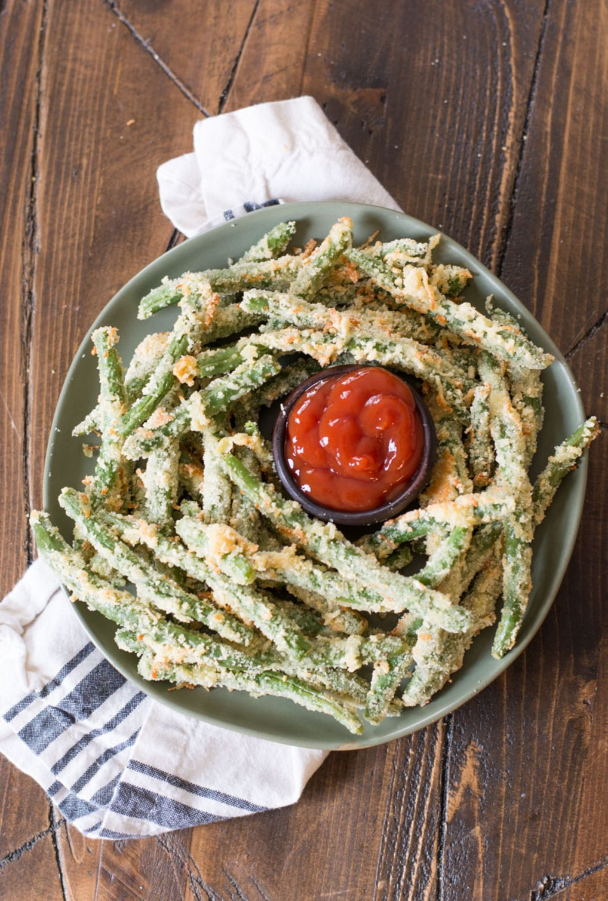 On a dark wooden table is a white and blue cloth with a green bowl on top. A pile of fried green beans surround a pot of red dip