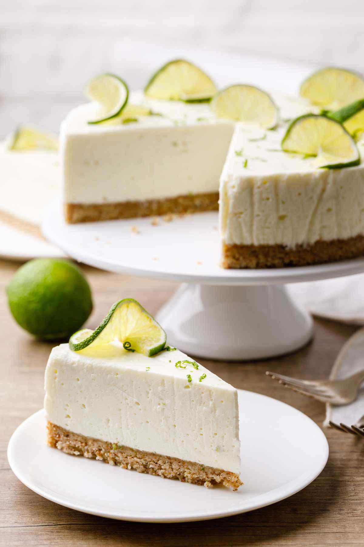 on a cake plate is a lime cheesecake with a portion taken out. on a plate below is one slice of the cheesecake with lime twist on top