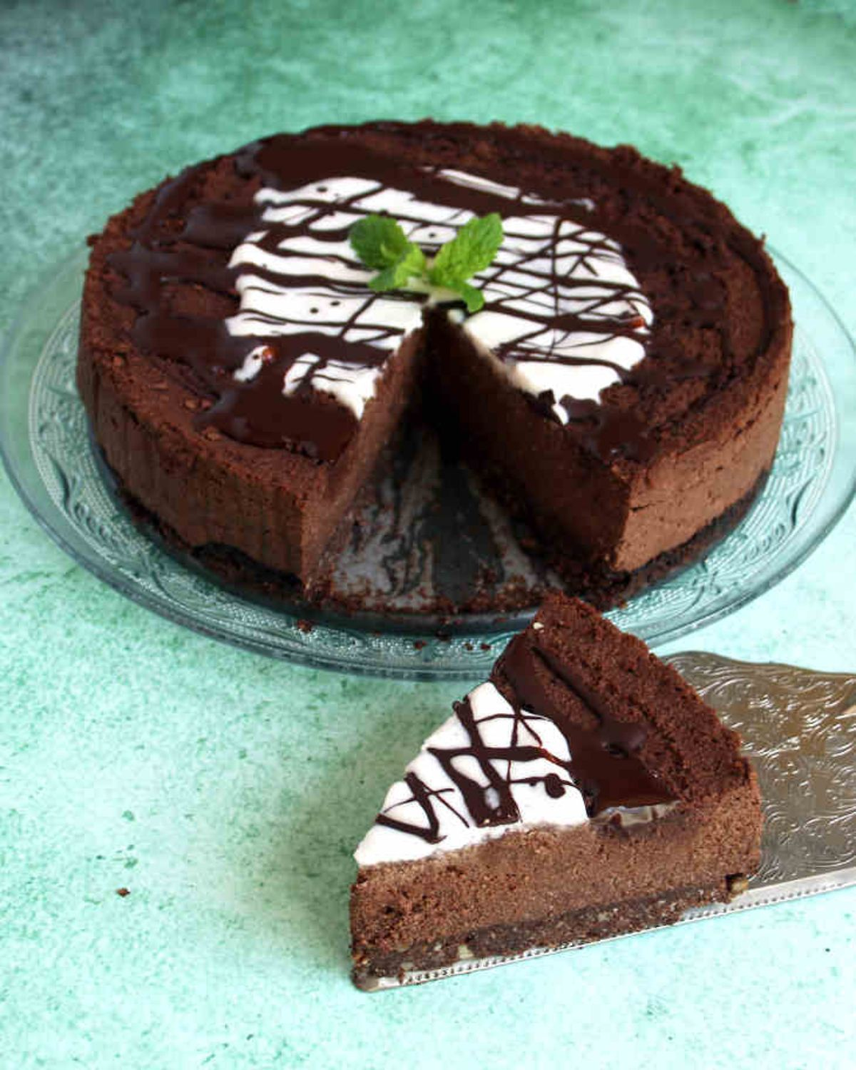 a dark chocolate cheesecake sits on a glass cake stand. It is toped with chocolate drizzle and some mint leaves. On a cake slice is the msising slice of cake