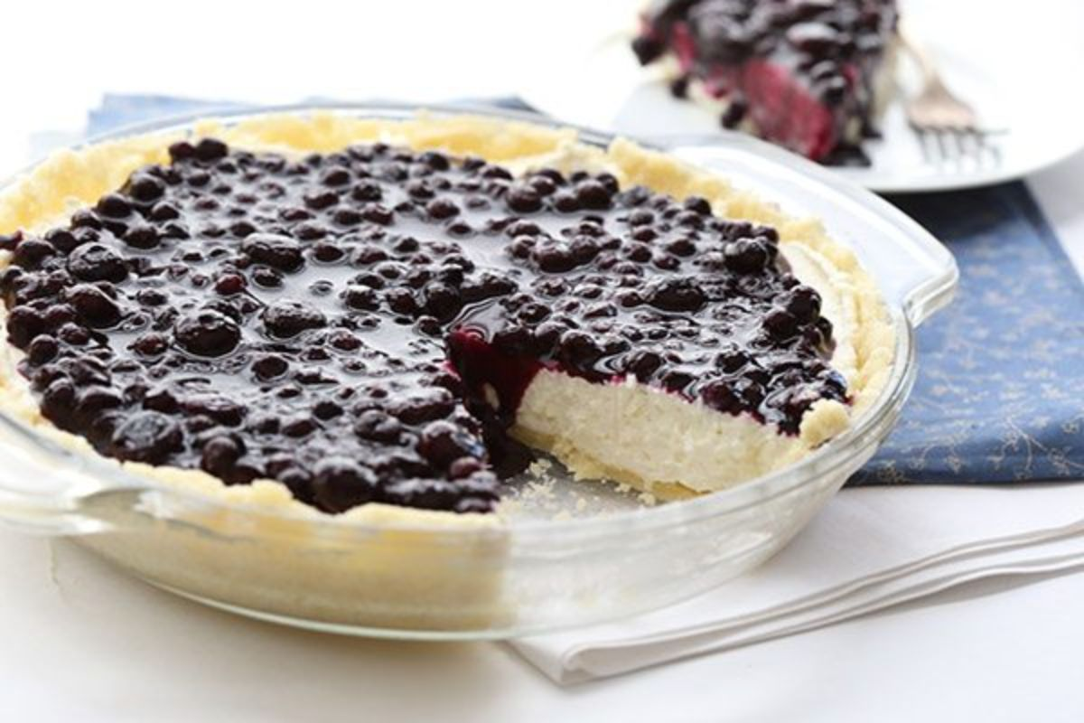 In a glass pie dish is a cheesecake covered in blueberry coulis, with a slice missing