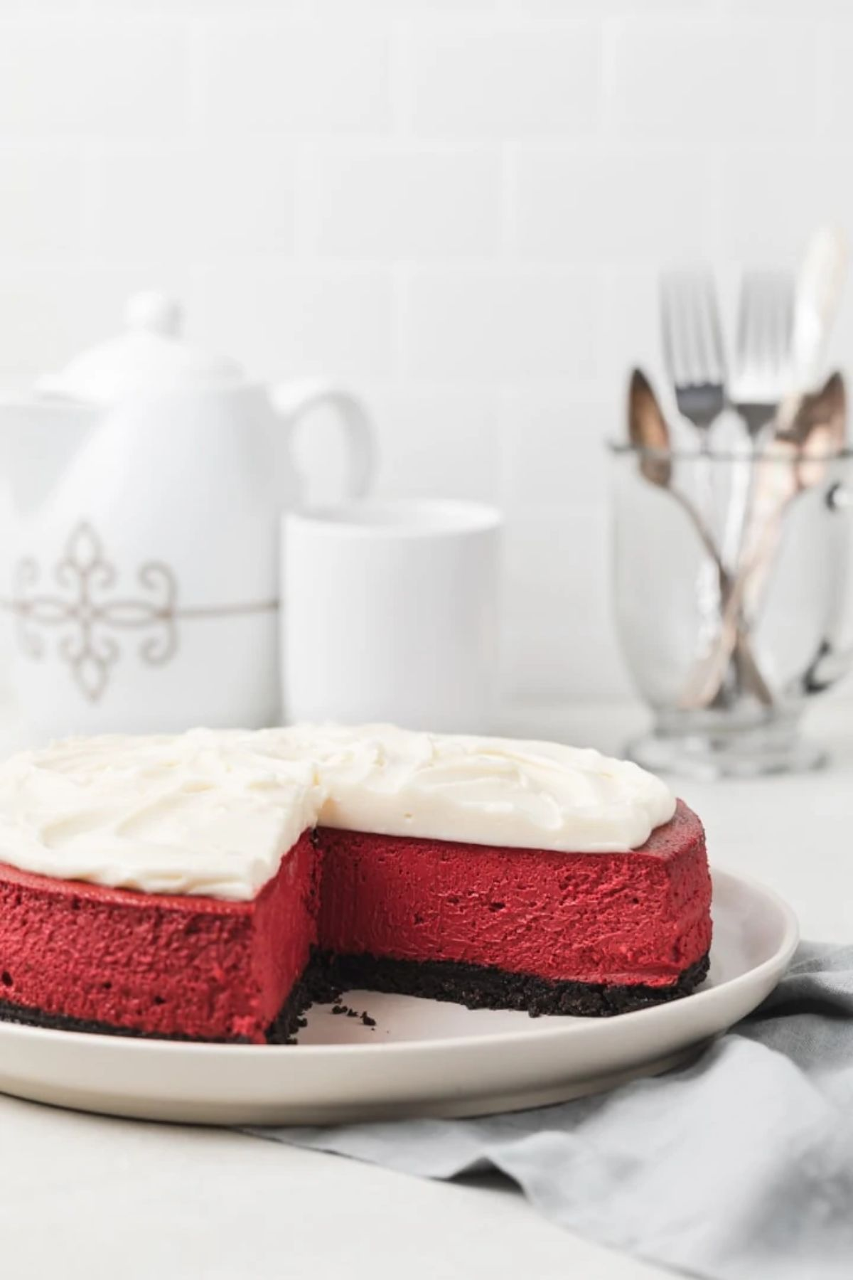 In front of a white china tea set is a red velvet cheeskecake with cream topping anfd a missingslice