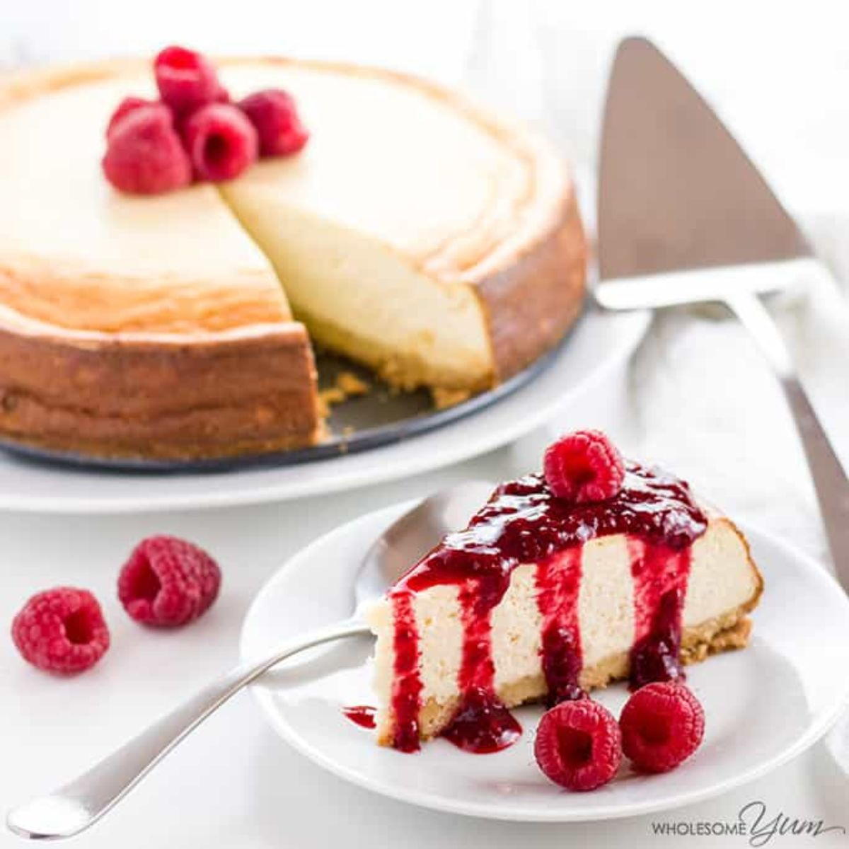 on a plate is a baked cheesecake with raspberries in the center. Below it is one slice of the cheesecake with raspberry coulis dirzzled over it. A cake slice os on the righ tof the photo