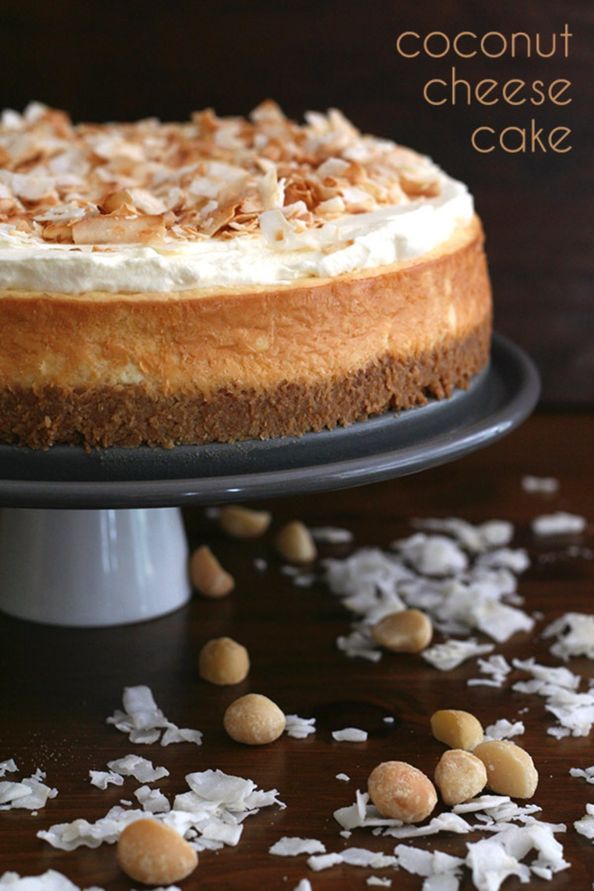 On a drak background a 3 layered cheesecake sits on a ckae stand sprinknled with flaked almonds