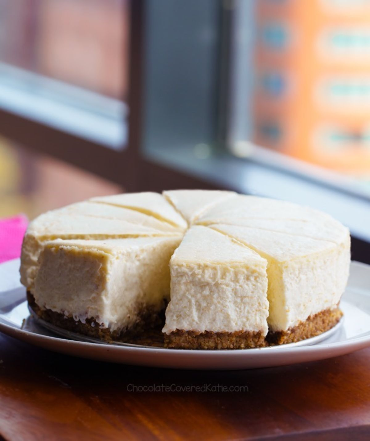 A plain cheesecake sits on a cake stand in front of a window. It has been cut into 8 slices