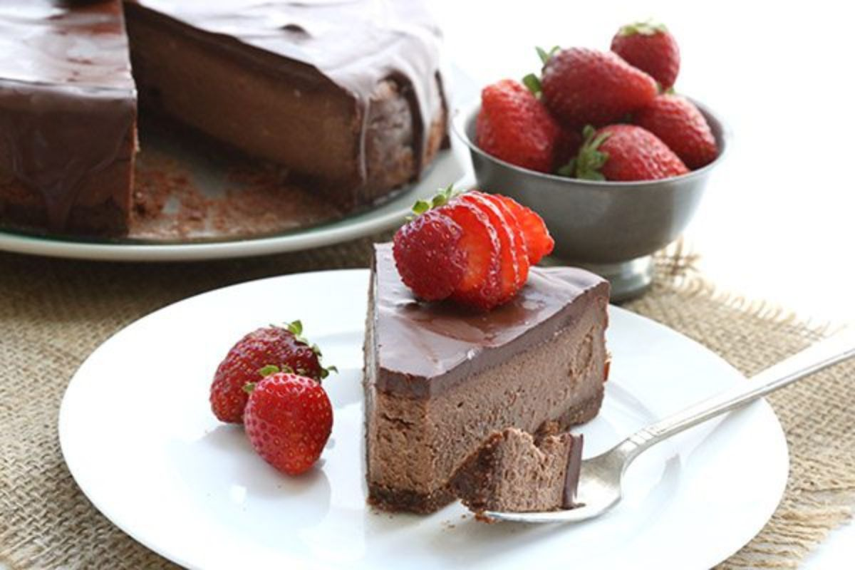 In the back of the photo is a chocolate cheesecake with a cdarker chocolate top and bottom with a slice cut out. The slice sits in frot on a white plate with strawberries on top and behind it is a bowl of strawberries