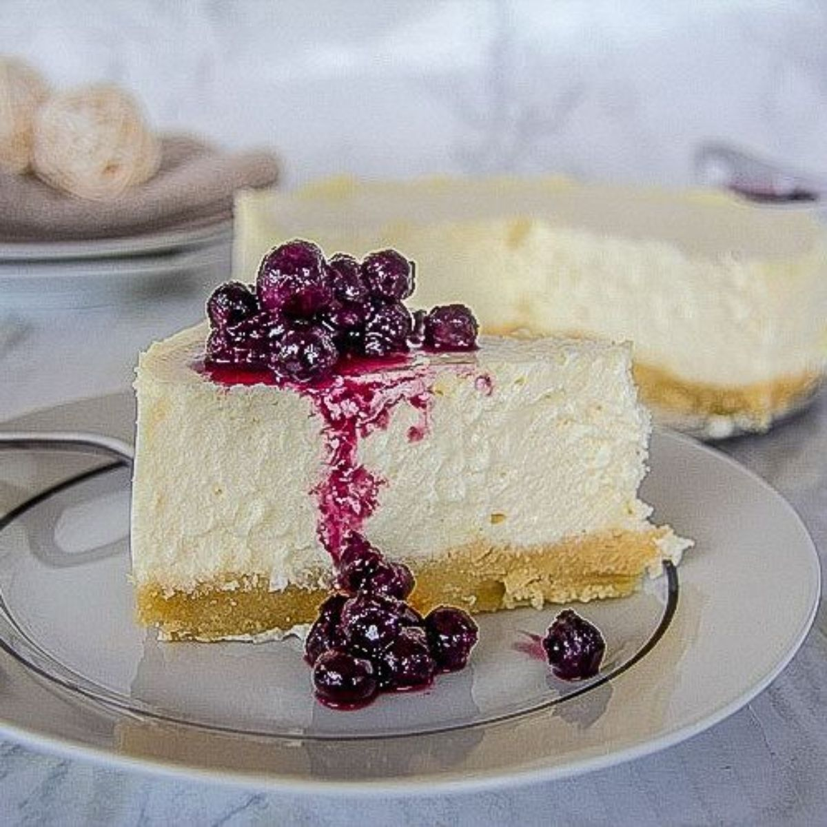 New York cheesecake slice sits on a plate with blueberry coulis srizzled on top