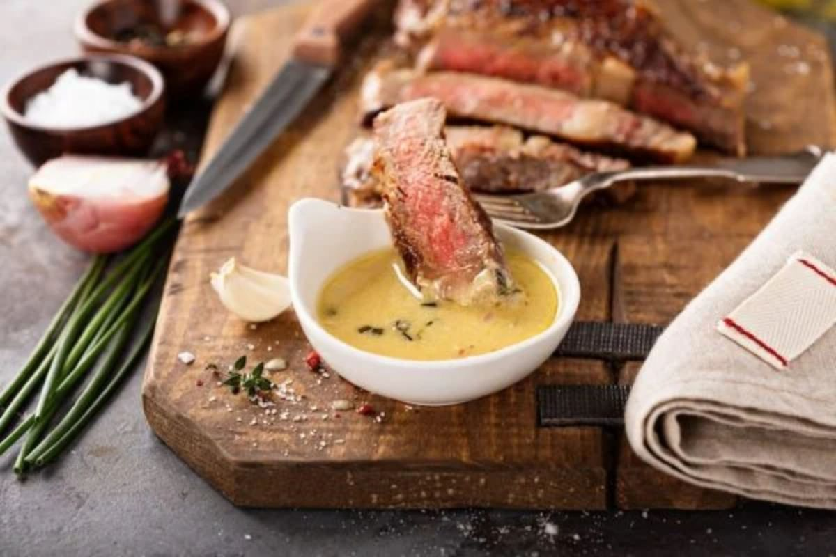 A chopping board sits on a gray s stone surface. On it is a sliced steak and a white pot full of yellow sauce. A fork with a piece of steak on the end is resting over the sauce. Also in shot are wooden bowls with salt and pepper, half an oinon, scallions, and a hessian cloth