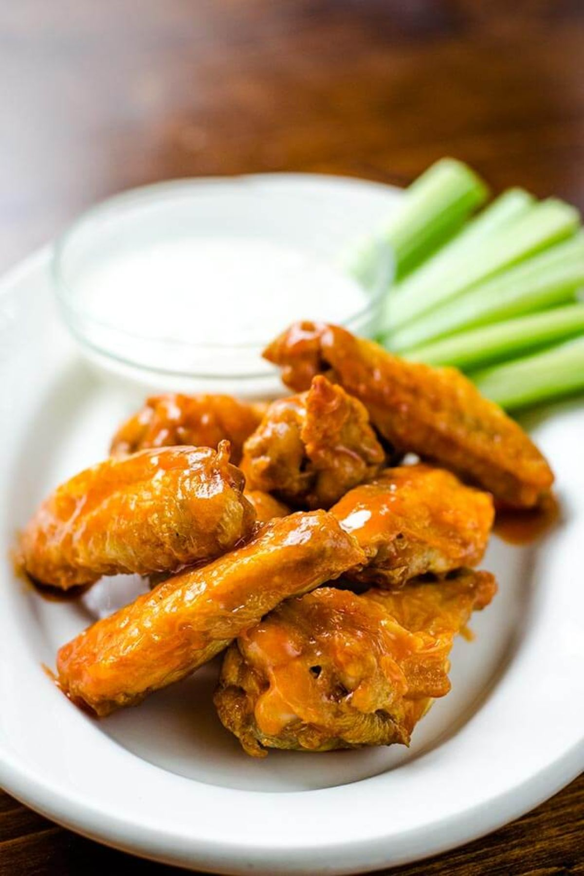 A small oval white plate has a pile of chicken wings on it, with a glass ot of white sauce and celery sticks in the background