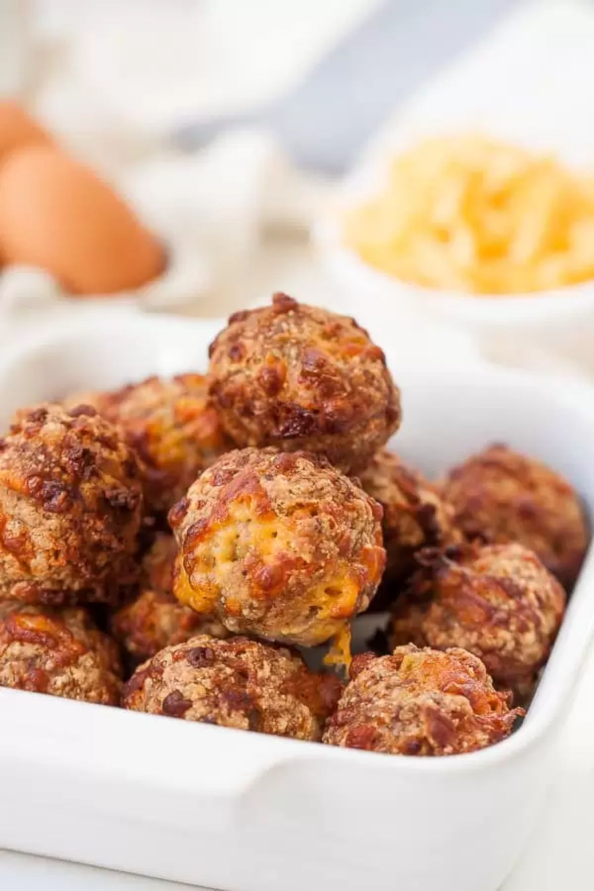 A rectangular oval baking dish is filled with baked sausage balls. In the bacground are blurred pots of toppings and some eggs