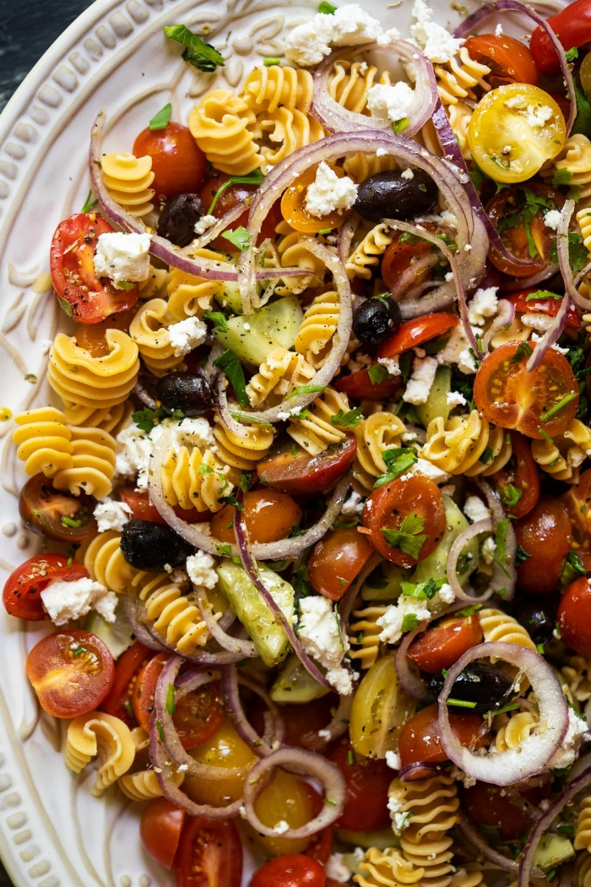 A partial shot of a white plate of spiralled pasta shapes mixed through with cherry tomatoes, red onion rings, cucumber and crumbled feta cheese