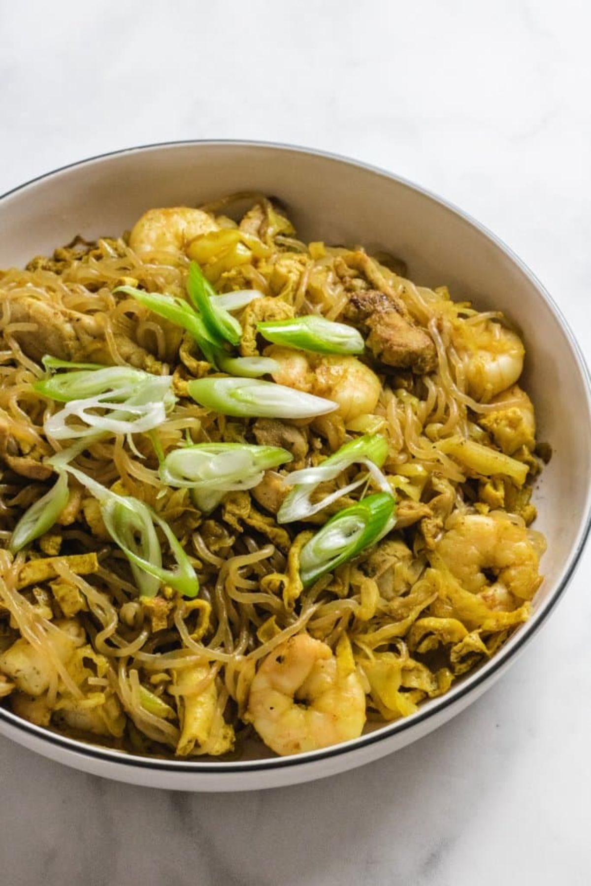 on a white surface is a white bowl with a blue rim. Inside is a pile of spaghetti with small peeled prawns, chopped spring onions and a yellowish sauce