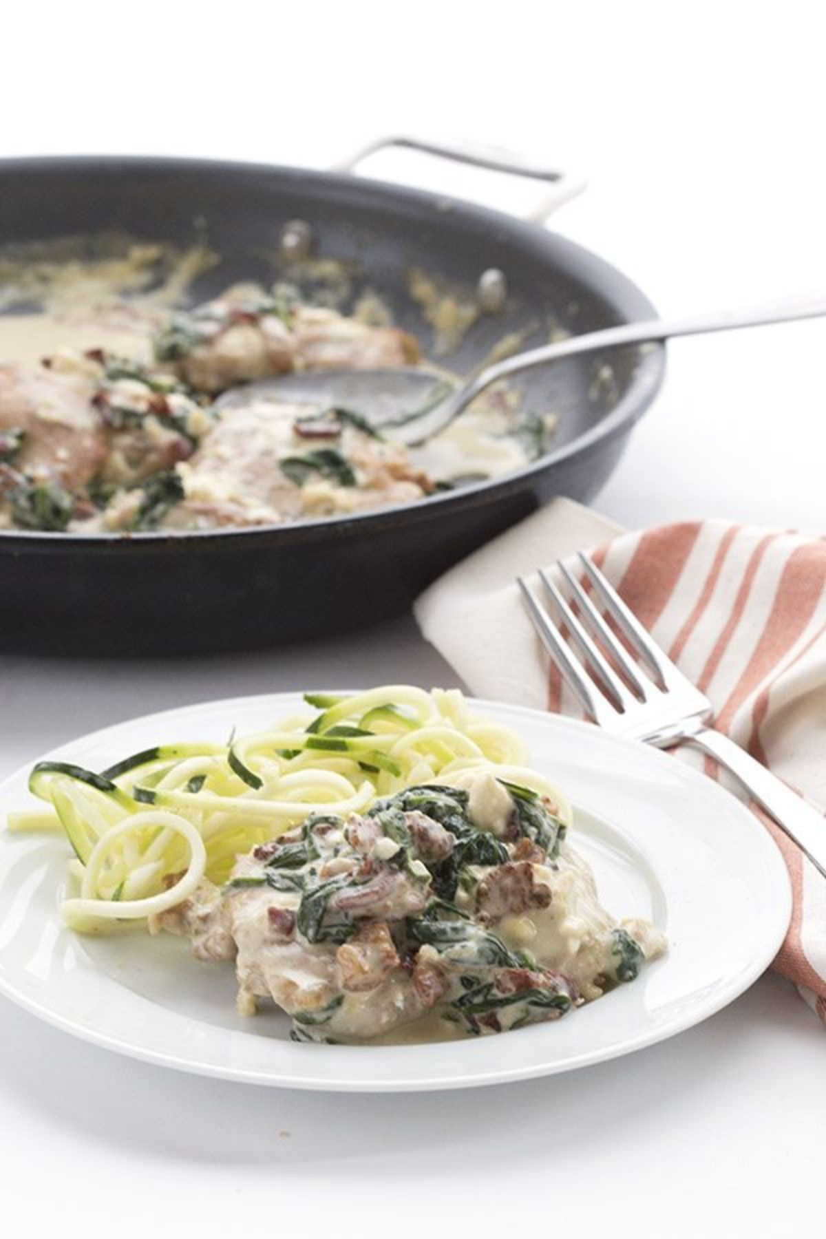 a white ocuntertop on which sits a dark gray skillet containing meat in a creamy sauce. In teh foregraound is a white plate with some of that meat and sauce, green wilted leaves and some spiralized courgette
