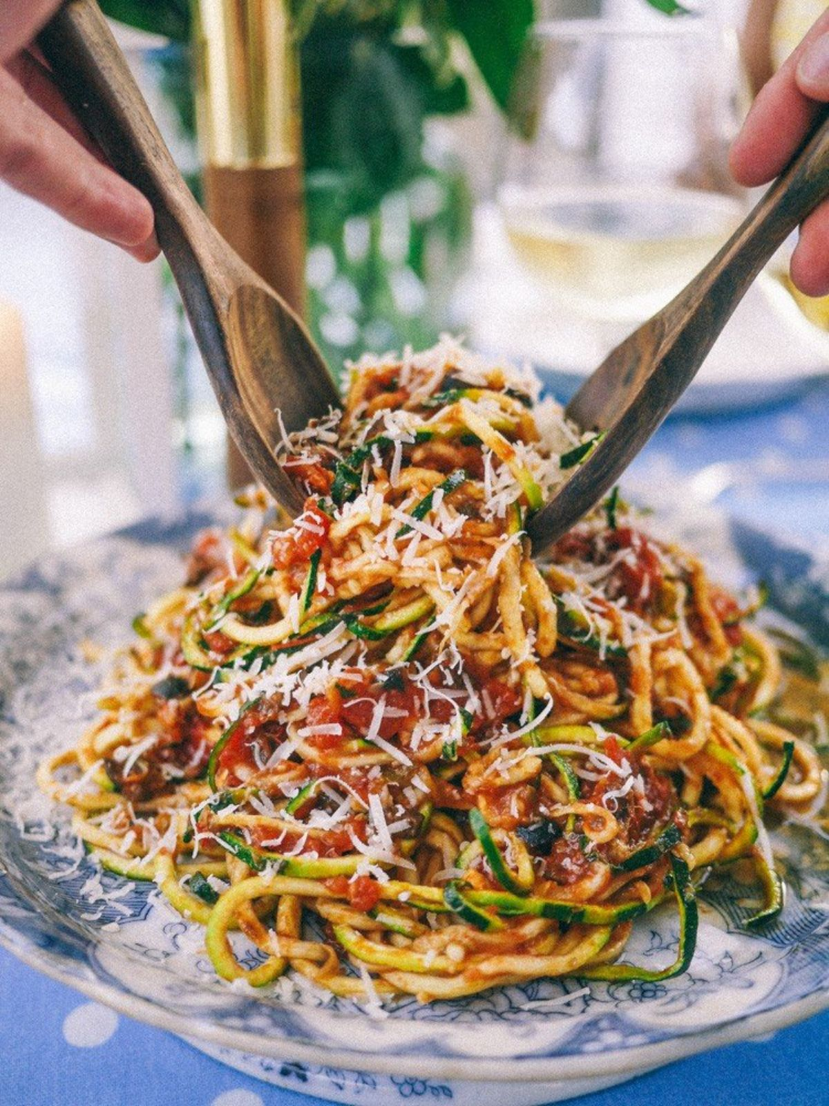 on a light blue tablecloth with white spots is a delft style dish. On top of it is some spiralized courgette covered in tomato sauce and parmesan cheese. Two wooden serving spoons are being hed by two hands digging in to the pasta