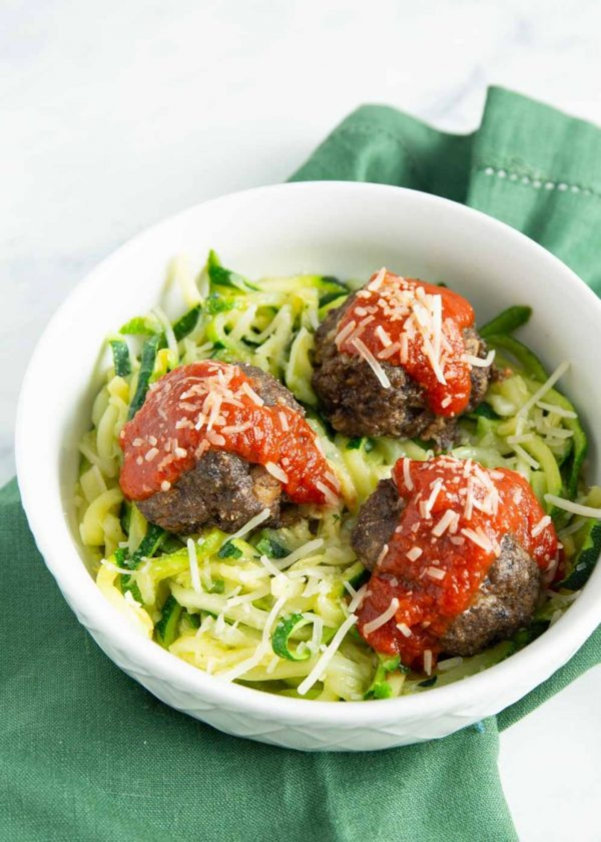 a white surface with a green cloth on top. On top of this is a white bowl filled with courgetti, 3 large meatbalss and 3 blobs of tomato sauce