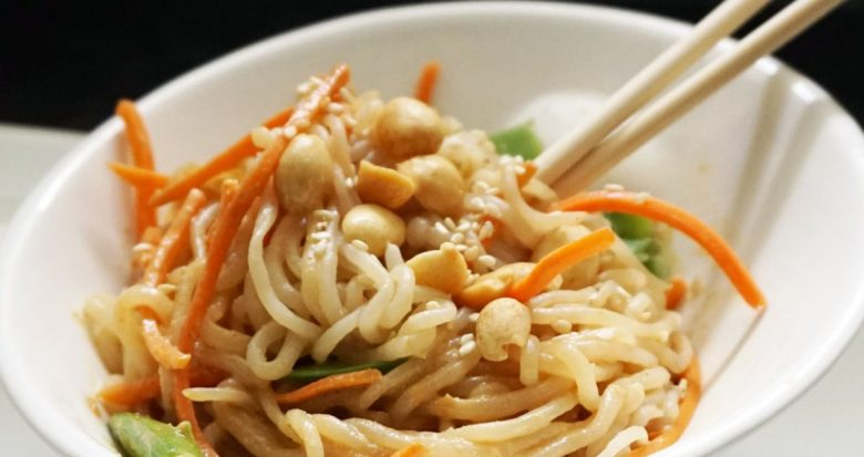 a white bowl with pale noodles mixed with matchstick carrots and leaves. Cashews are scattered on top and two chopsticks are sticking out of the dish