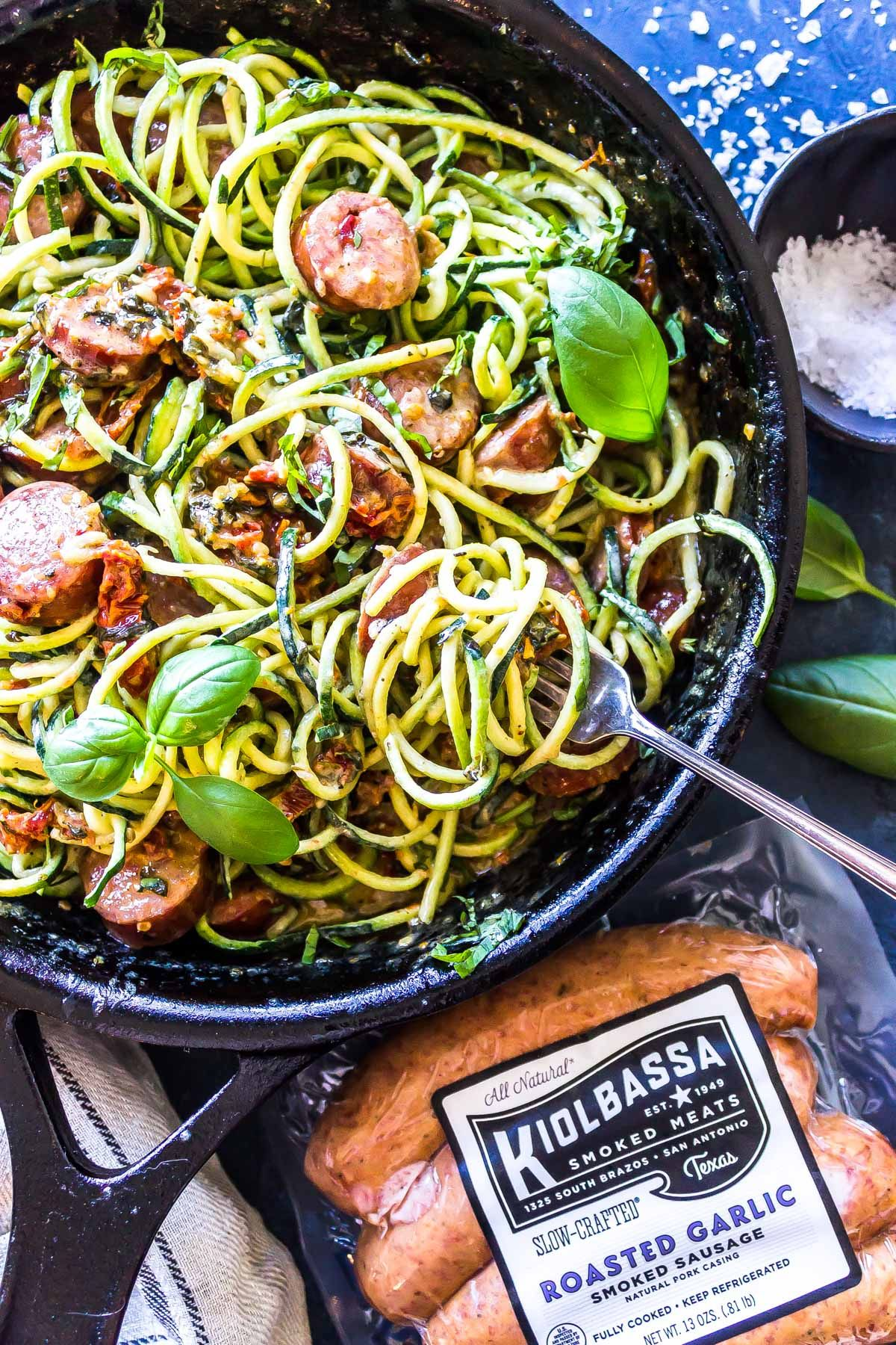 a black skillet contains courgetti mixed with sliced sausage. In the foreground is a packet of the Kiolbassa Roasted Garlic smoked sausage