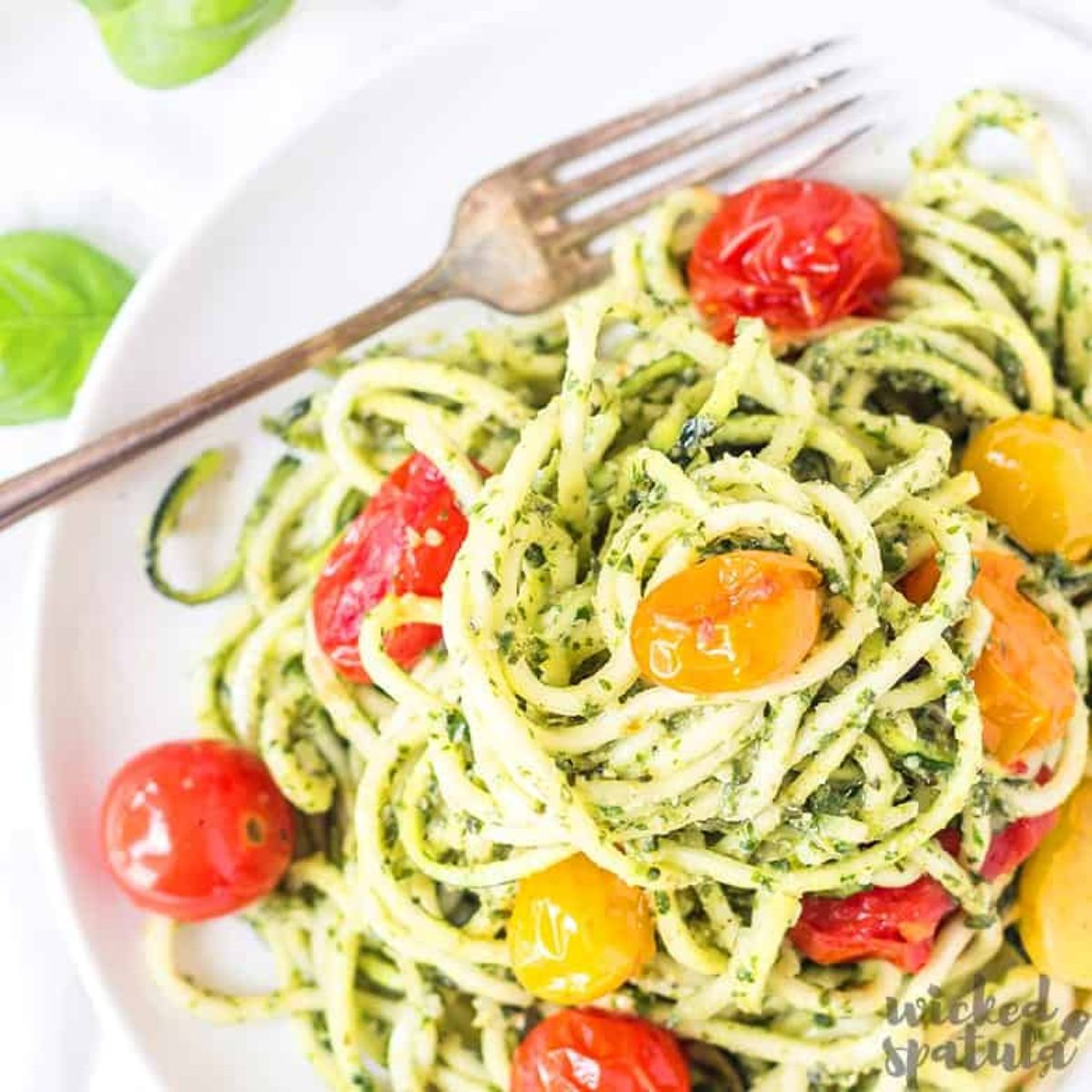 A partial shot of a white bowl filled with spaghetti mixed with pesto sauce and cherry tomatoes. A metal fork is at the top of the bowl