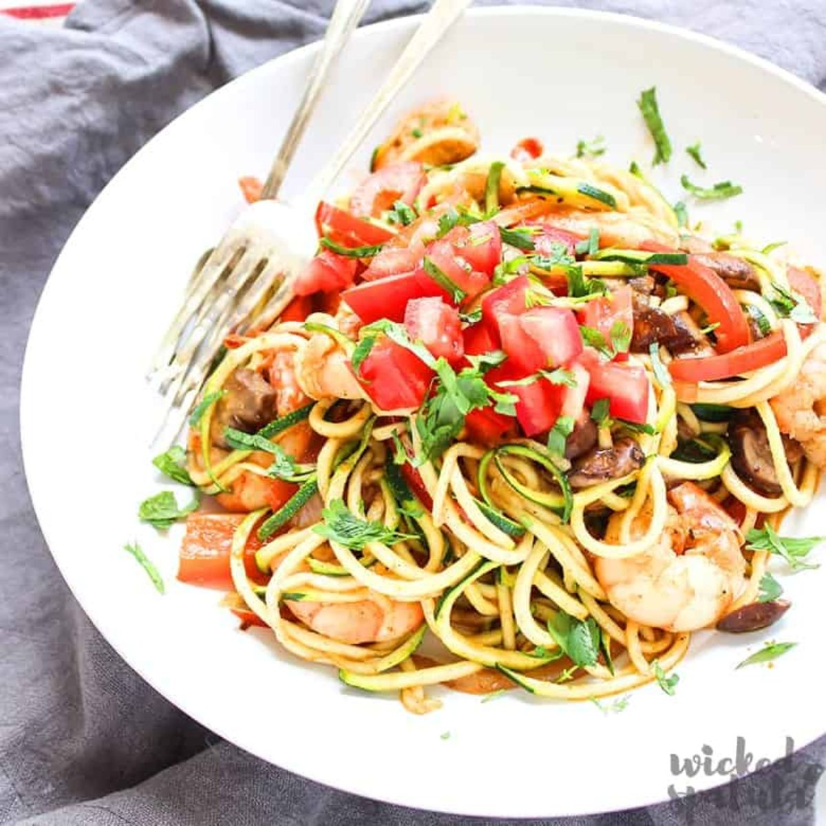 on a rumpled gray cloth is a white bowl filled with courgetti, mixed with proawns, chopped tomatoes and basil