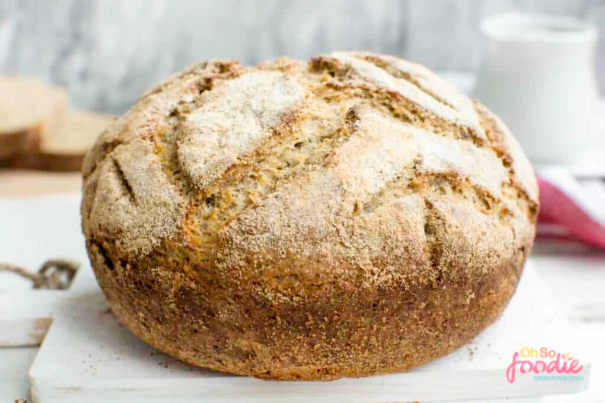 On a stone board is a round loaf of bread with a cracked top and sprinkled with flour