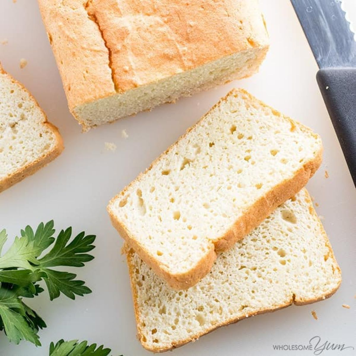 On a white surface is a partial shot of a rectangular loaf of white bread, two cut slices are in the front of the shot on top of each other. Parsely is on the left of the shot