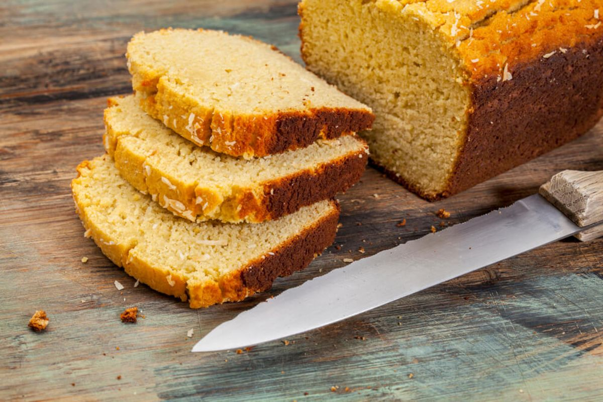 On a wooden table is a rectangular loaf of bread with a yellow tinge. 3 slices are laid on top of each other and a bread knife is in the front of the shot