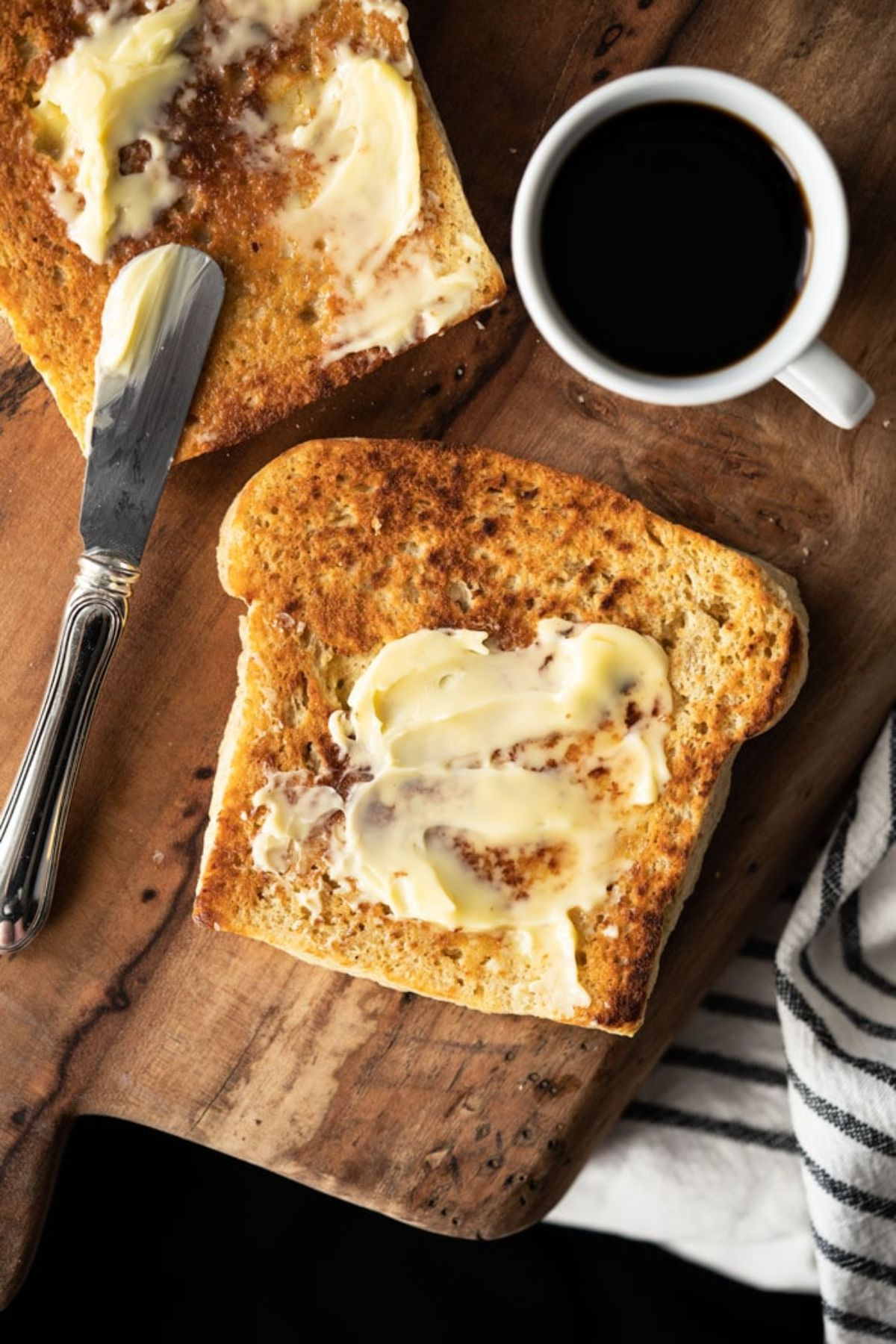On a wooden board are 2 slices of bread with butter spread on them. A butter knife rests on one of the slices and a white cup of black coffee is at the top