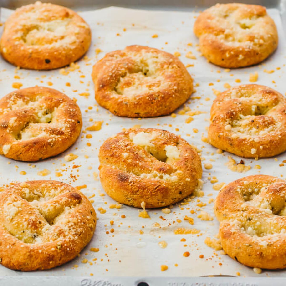 On a baking sheet are 8 round twisted rolls sprinkled with cheese